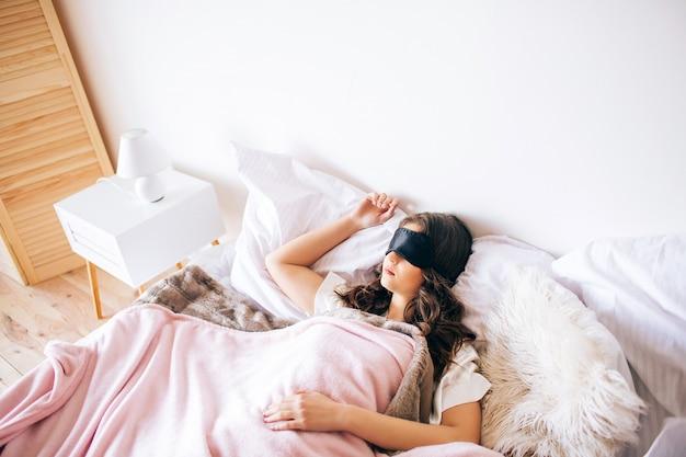 Dunkelhaarige schöne junge brünette, die in ihrem bett schläft. schwarze schlafmaske auf den augen. allein im schlafzimmer. träume.