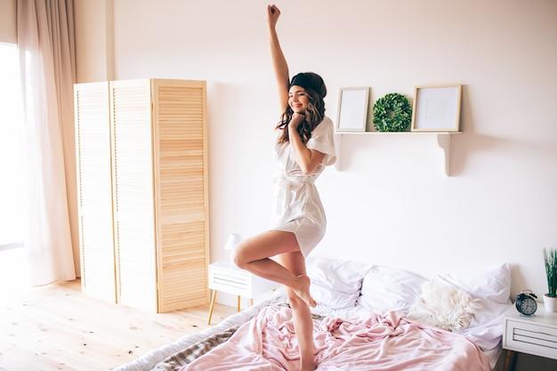Dunkelhaarige schöne junge brünette wacht in ihrem bett auf. attraktives modell, das die hand streckt und tanzt. allein im schlafzimmer. positiver glücklicher morgen.