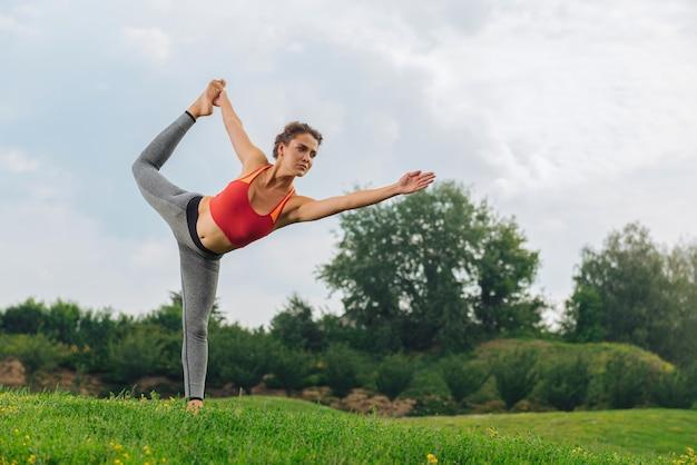 Dunkelhaarige turnerin, die sich entspannt fühlt, während sie ihr gleichgewicht und ihre dehnung verbessert