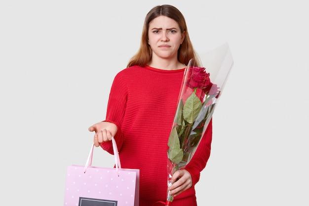 Dunkelhaarige unzufriedene frau runzelt die stirn, mag geschenk nicht, hält geschenktüte in einer hand und blumenstrauß in der anderen, isoliert auf weiß, trägt roten freizeitpullover. ich mag es nicht