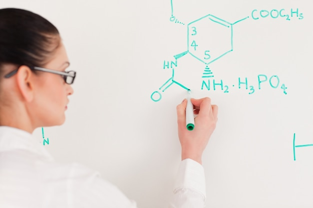 Dunkelhaarige wissenschaftlerfrau, die eine formel auf ein weißes brett schreibt