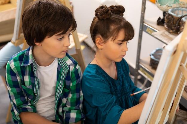 Dunkelhaariger bruder beobachtet seine schwester beim malen in der kunstschule