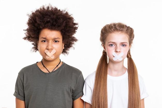 Dunkelhaariger freund. verängstigte verwirrte junge kinder, die mit zusammengeklebten mündern schulter an schulter zusammenstehen