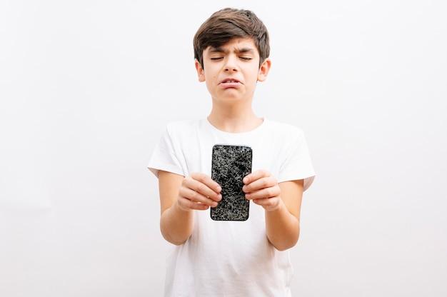 Dunkelhaariger junge, der ein gebrochenes smartphone mit einem weinenden ausdruck hält