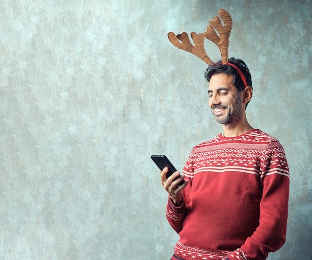 Dunkelhaariger junge mit kurzem grauem bart in einem roten weihnachtspullover und rentiergeweih-stirnband mit blick auf das smartphone in der hand