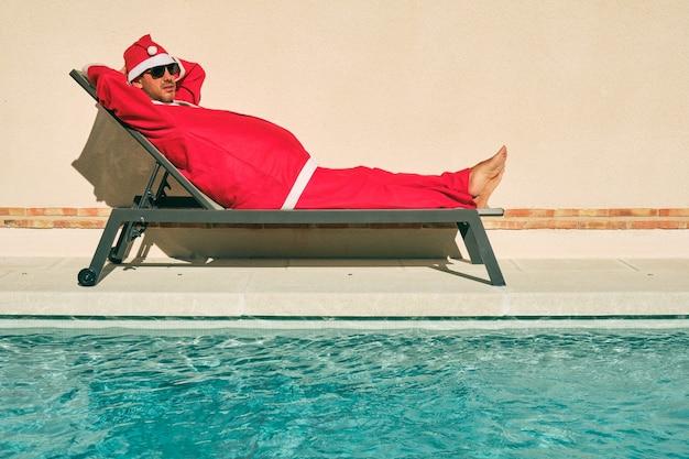Dunkelhaariger junge mit schwarzer sonnenbrille, verkleidet als weihnachtsmann, der in einer hängematte am rand eines swimmingpools in der sonne liegt