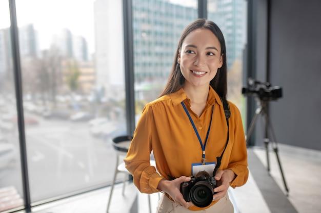 Dunkelhaariger junger süßer reporter, der eine kamera hält, die nett lächelt