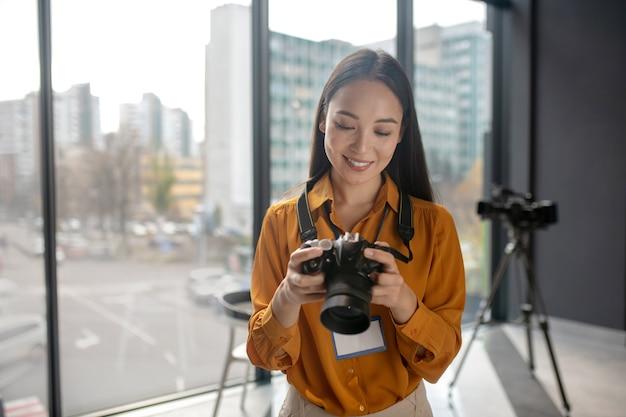 Dunkelhaariger junger süßer reporter, der fotos in der kamera betrachtet
