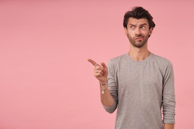 Dunkelhaariger mann mit bart stehend, mit dem zeigefinger beiseite zeigend, mit zweifelndem gesicht und spitzenden lippen schauend