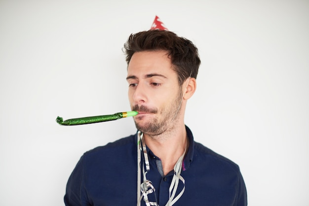 Dunkelhaariger mann mit partyhorngebläse