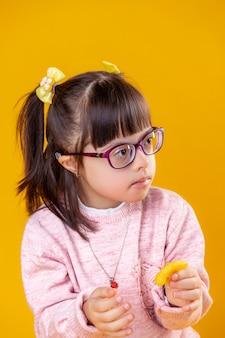 Dunkelhaariges mädchen mit down-syndrom, das orangefarbene chips in der hand trägt