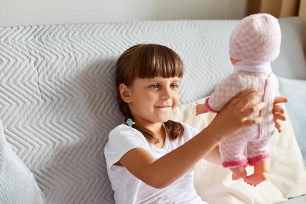 Dunkelhaariges weibliches kind, das weißes t-shirt trägt, hat zöpfe, die ihre puppe anheben, ihr spielzeug mit einem lächeln betrachten und alleine spielen, während sie zu hause auf dem sofa sitzen.
