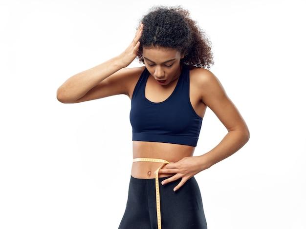 Dunkelhäutige afroamerikanerin posiert in einem trainingsanzug und misst ihre taille