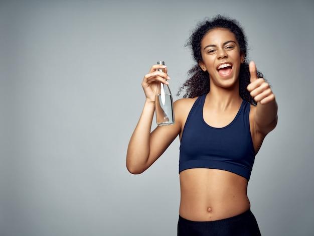 Dunkelhäutige afroamerikanerin posiert in einem trainingsanzug und treibt sport im studio
