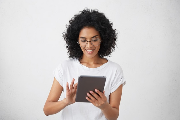 Dunkelhäutige lächelnde charismatische und schöne studentin, die modernes gerät hält, tablet für videoanruf mit ihren freunden verwendet, lustige videos ansieht oder hausaufgaben macht, plaudert