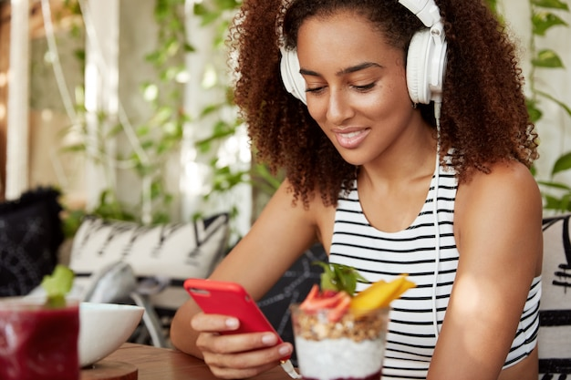 Dunkelhäutige mischlinge in stilvollen kopfhörern lädt hörbuch auf handy, verbringt freizeit im café, hört elektronische musik. glückliche frau wählt lieblingslied in der wiedergabeliste.
