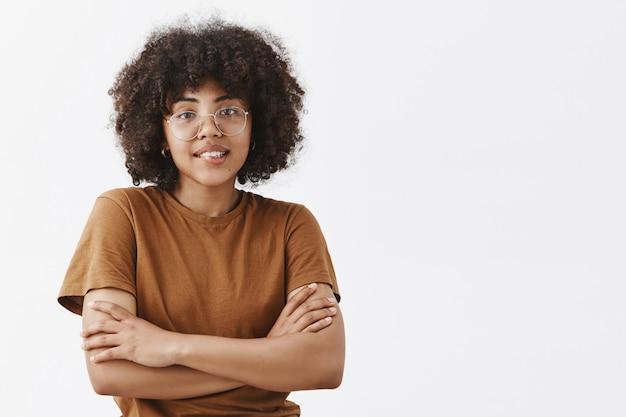 Dunkelhäutige teenager-frau in transparenter brille und trendigem braunem t-shirt, die sich kalt fühlt, die hände auf der brust kreuzt und mit freundlichem und höflichem ausdruck lächelt