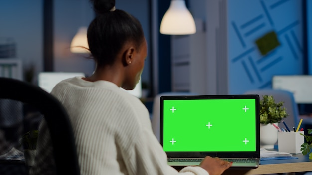 Dunkelhäutiger freelancer, der vor greenscreen-display arbeitet