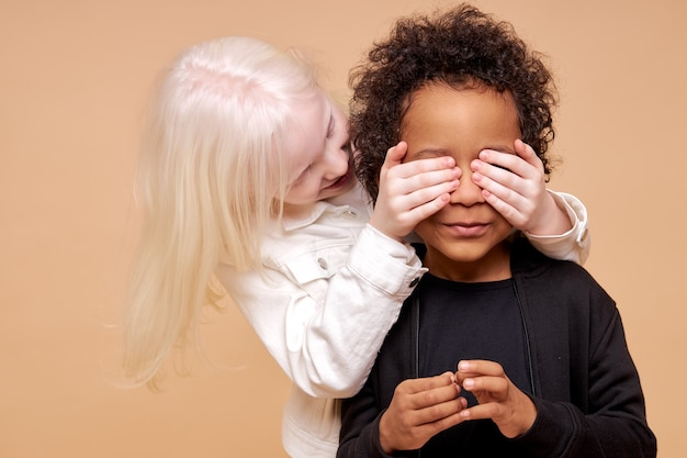 Dunkelhäutiger junge und albino-mädchen spielen verstecken