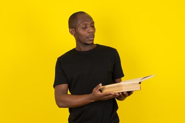 Dunkelhäutiger junger mann, der buch hält und an gelbe wand denkt