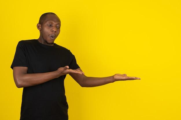 Dunkelhäutiger junger mann, der etwas an gelber wand zeigt