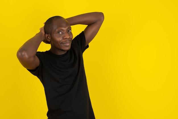 Dunkelhäutiger junger mann, der seine hände hinter dem kopf an einer gelben wand steht