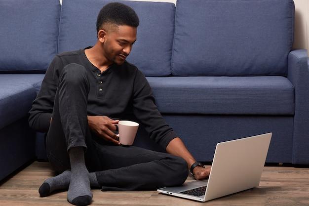 Dunkelhäutiger junger mann, der zu hause mit seinem laptop arbeitet, hält tasse mit heißem getränk und sitzt nahe couch auf dem boden