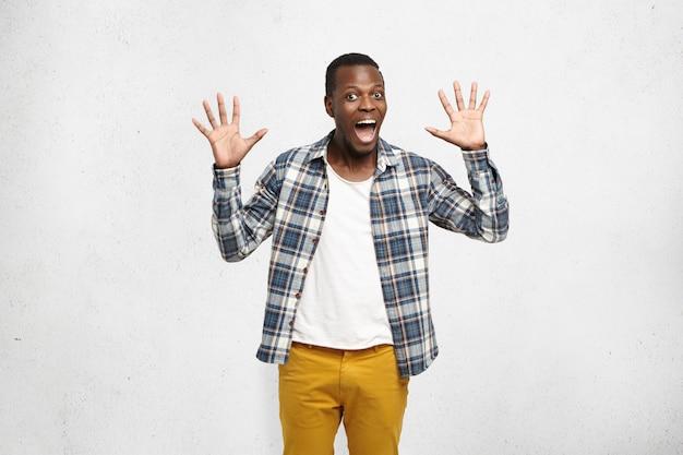 Dunkelhäutiger junger mann in stilvoller kleidung, der eine grußgeste zeigt oder mit beiden händen high five gibt und mit fröhlichem und aufgeregtem ausdruck aussieht. körpersprache