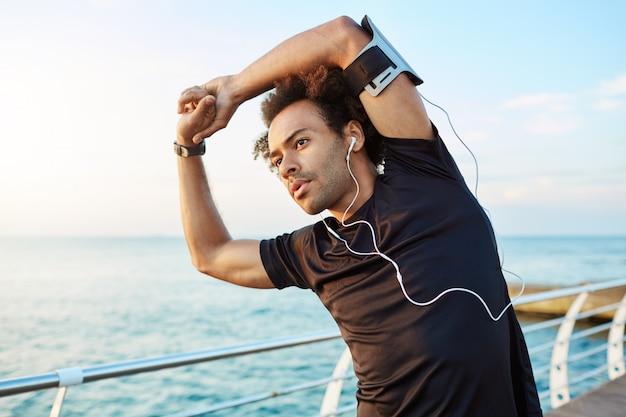 Dunkelhäutiger männlicher läufer mit wunderschönem athletischen körper und buschiger frisur, der die muskeln dehnt und seine arme hebt, während er sich vor dem morgendlichen training aufwärmt.