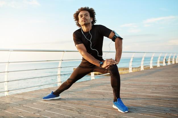 Dunkelhäutiger männlicher läufer mit wunderschöner körperwärmung vor dem cardio-training. männlicher athlet in der sportbekleidung, die beine mit longe-kniesehnen-streckübung durch das meer im morgensonnenlicht streckt