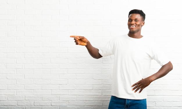Dunkelhäutiger mann, der finger auf die seite zeigt und ein produkt darstellt