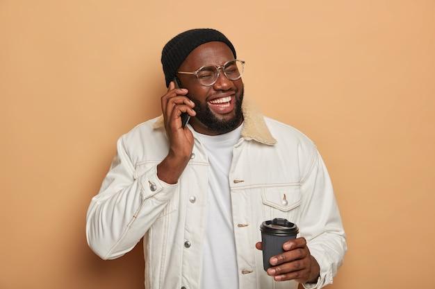 Dunkelhäutiger mann hat lustiges telefongespräch, lacht während des telefongesprächs