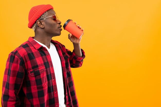 Dunkelhäutiger mann in einem karierten roten hemd trinkt kaffee seitlich gelb mit raum