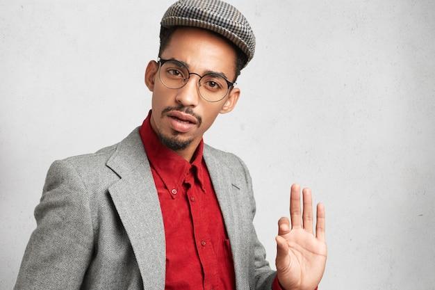 Dunkelhäutiger mann in runder brille, trägt altmodische mütze und hemd, zeigt ok-zeichen,