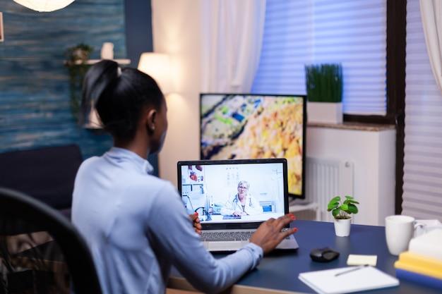 Dunkelhäutiger patient im gespräch mit arzt im zuge einer videokonferenz ab spät in die nacht. frau, die während der virtuellen konsultation über symptome diskutiert.
