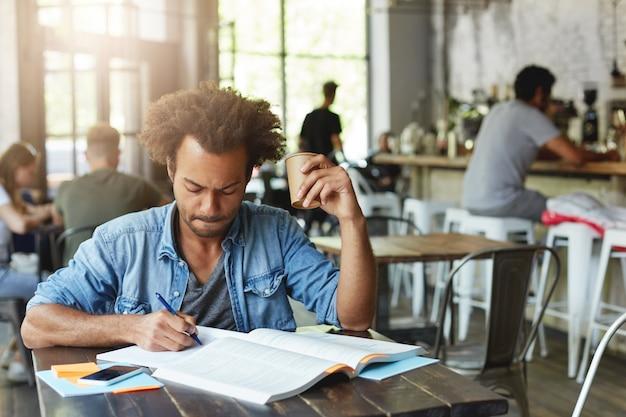 Dunkelhäutiger student männlich mit lockiger afrikanischer frisur, die hausaufgabe macht und sich auf das schreiben einer lektion in einem heft vorbereitet, das kaffee in der cafeteria trinkt und ernsthaft aussieht, konzentriert
