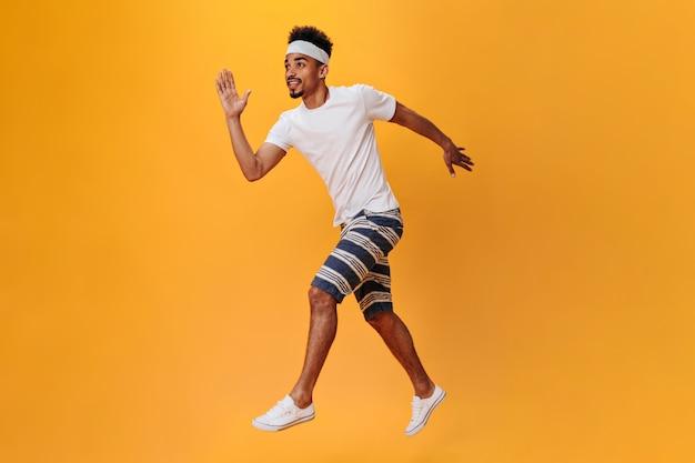 Dunkelhäutiger typ in shorts und t-shirt läuft an einer orangefarbenen wand. sportler trainiert isoliert
