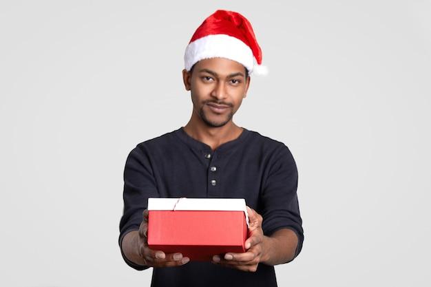 Dunkelhäutiger weihnachtsmann mann hält geschenkbox, gratuliert ihnen mit neujahr, modelle gegen weiße wand. fokus auf gegenwart. ethnizität und feiertagskonzept. afroamerikaner männlich im festlichen hut