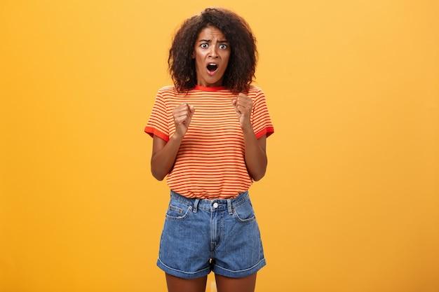 Dunkelhäutiges erwachsenes mädchen mit geballten fäusten der afro-frisur, die den mund öffnen und besorgt über die orangefarbene wand schauen