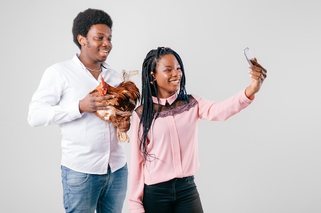 Dunkelhäutiges lustiges paar, das selfie mit huhn in den händen macht