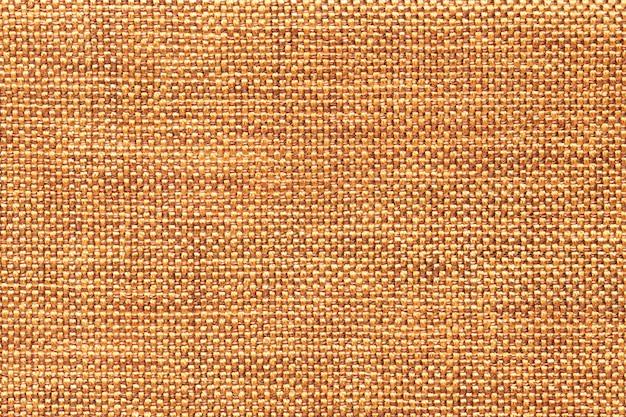 Dunkelorangeer textilhintergrund mit kariertem muster, nahaufnahme. struktur des gewebemakros.