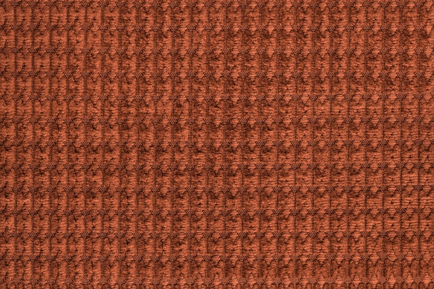 Dunkeloranger hintergrund vom weichen flauschigen gewebeabschluß oben. textur von textilien makro