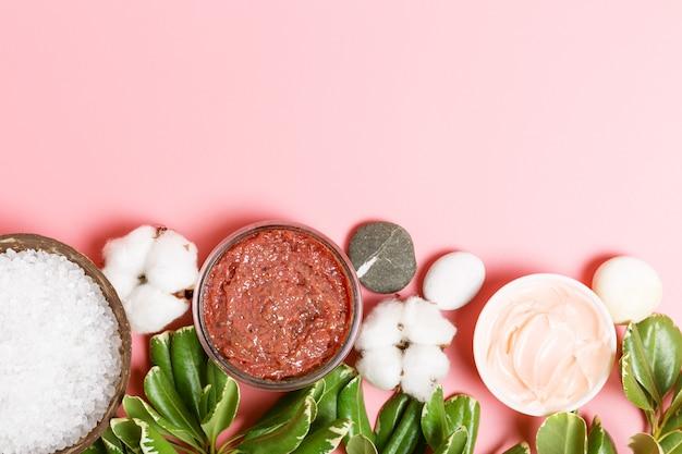 Dunkelrosa körperpeeling, creme, badesalz, kerzen, baumwolle und grüne blätter auf einem rosa hintergrund. spa- und körperpflegekonzept. schönheitswohnung lag.