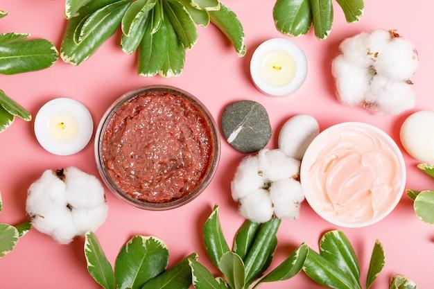 Dunkelrosa körperpeeling, creme, kerzen, baumwolle und grüne blätter auf einem rosa hintergrund. spa- und beauty-konzept. flach liegen, draufsicht.