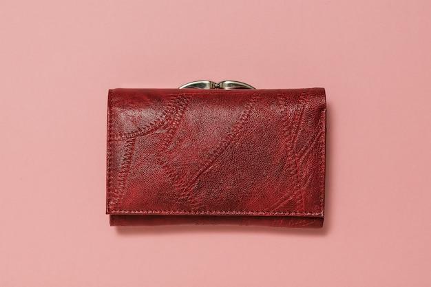 Dunkelrote damen leder geldbörse auf rosa hintergrund. modisches damenaccessoire.