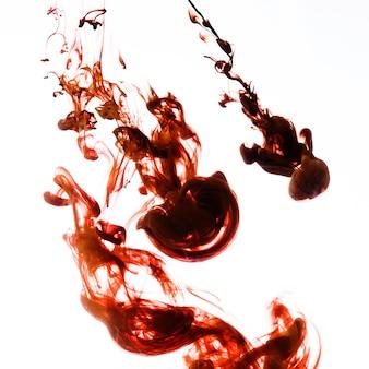 Dunkelrote tröpfchen, die in wasser fließen