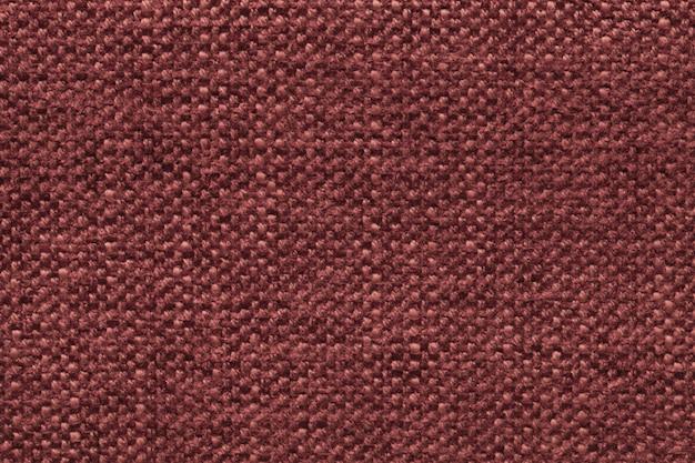 Dunkelroter gestrickter wollhintergrund mit einem muster aus weichem, flauschigem stoff. beschaffenheit der textilnahaufnahme.