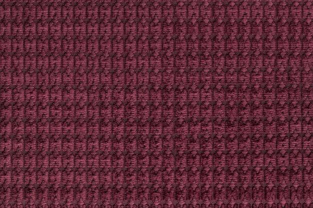 Dunkelroter hintergrund vom weichen flauschigen gewebeabschluß oben. textur von textilien makro