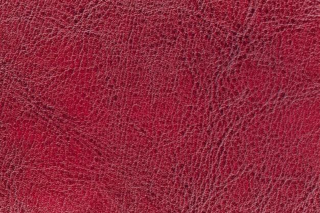 Dunkelroter lederner beschaffenheitshintergrund, nahaufnahme. rubinroter gebrochener hintergrund von der faltenhaut
