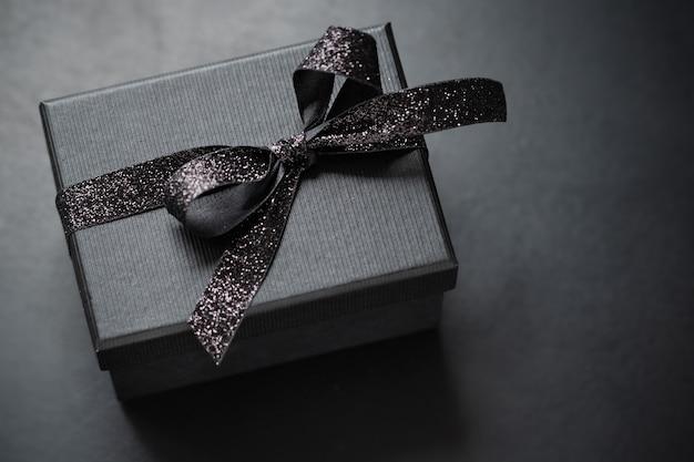 Dunkelschwarze geschenkbox mit schwarzem band auf dunklem hintergrund. nahaufnahme